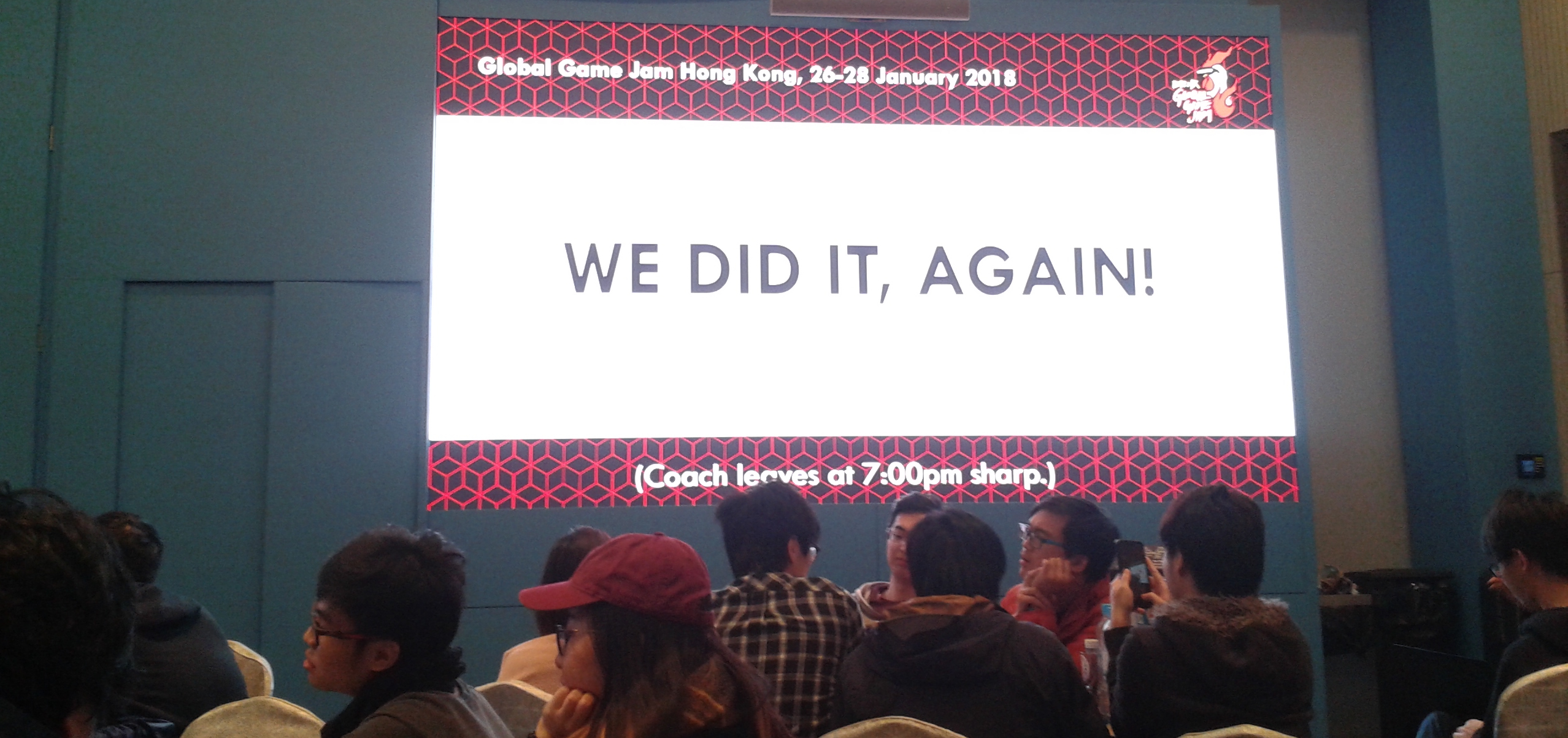 "GGJ Venue with a big screen showing a Powerpoint slide with the words ""WE DID IT, AGAIN!"""