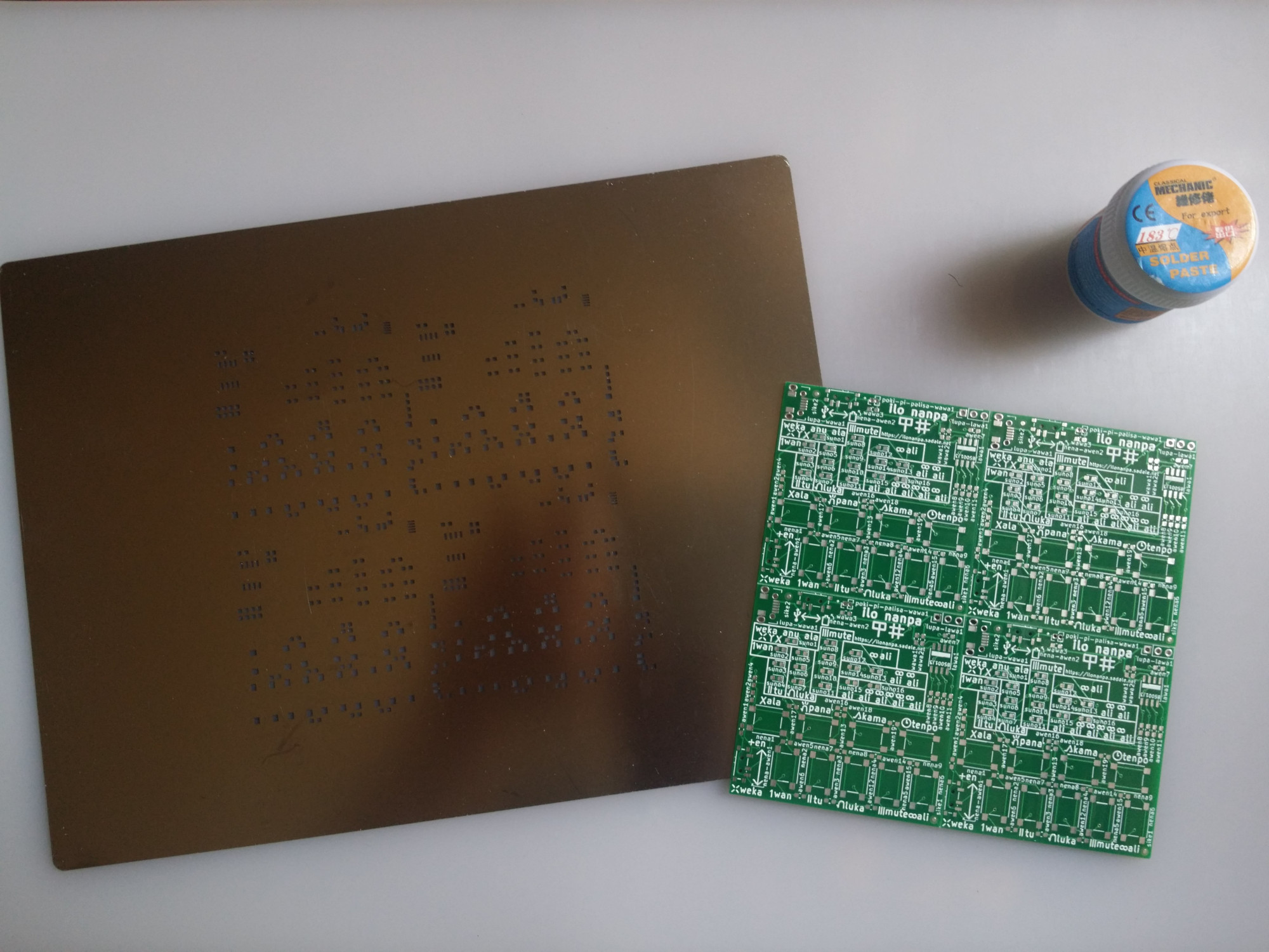 a jar of solder paste, panelized PCB and a stencil on a heat-resistant mat